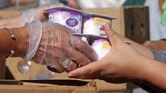 A volunteer hands yogurt to a recipient as over 120 families received food as the Food Bank of Westchester's mobile pantry distributed donated food outside the White Plains library in October 2015.