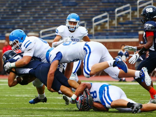 Catholic Central's defense of Tyler St. Clair (top),