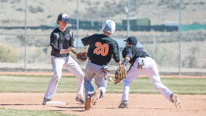 Kirtland Central's Cochise Sorrelhorse, right, tosses the ball to Zach Van Duran to register an out against Aztec baserunner Garrett Ray (20) during a game on Saturday in Aztec.