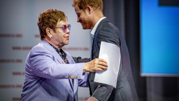 Elton and Harry embrace.