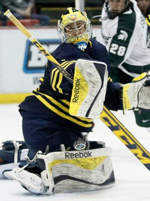Michigan goalie Steve Racine deflects a shot by Michigan State during the second period of an NCAA college hockey game in the Big Ten Conference tournament Friday, March 20, 2015, in Detroit. Racine had 26 saves in a 4-1 win over Michigan State.