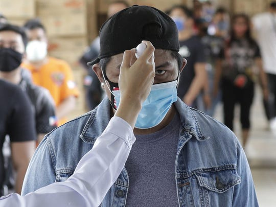 Temperatures are checked before people enter a local city hall during a community quarantine aimed to prevent the spread of the new coronavirus in Manila, Philippines, Tuesday, March 24, 2020. For most people the new coronavirus causes only mild or moderate symptoms, but for some it can cause more severe illness. (AP Photo/Aaron Favila)