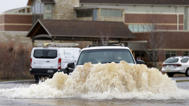 A driver maneuvers through flooding waters while exiting Neuroscience Group Monday in Neenah.