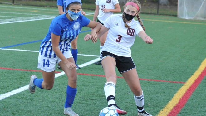 Quincy's Grace Akkara, left, tries to push away North Quincy's Paige Grippi as she moves the ball downfield during girls soccer at Veterans Stadium in Quincy, Wednesday, Oct. 14, 2020.