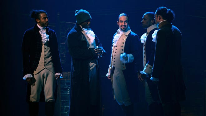 """In this image released by Disney Plus, from left, Daveed Diggs, Okieriete Onaodowan, Lin-Manuel Miranda, Leslie Odom Jr. and Anthony Ramos appear in a filmed version of the original Broadway production of """"Hamilton."""""""