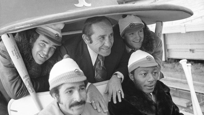 """FILE - In this January 1973 photo, New York Mets manager Yogi Berra, center, poses in the team cart at Shea Stadium in New York with four who signed with the baseball team earlier in the day. They are, back row and from left: Ed Kranepool, Berra, and Tug McGraw. Front row, from left: Felix Millan and John Milner. Cleon Jones also signed, but was not present for the picture session. Bullpen buggies are rolling back, and Cleveland Indians manager Terry Francona is positively bug-eyed about the prospect. """"I love it. I love it. I love it,"""" he said Tuesday, March 6, 2018. Nearly a quarter-century since relievers stopped catching rides to the mound, the bullpen cart will become the latest retro feature to make a return to the big leagues."""