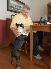 Roy Allen pets his dog C.J. at his home in Jay, Florida