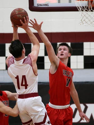 Valders' Jake Beinborn (11) tries to block the shot by New Holstein's Ryan Steffes (14), Tuesday, January 16, 2018, in New Holstein, Wis.