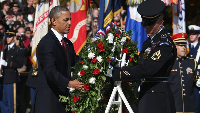 President Obama positions a commemorative wreath during a ceremony on Veterans Day at the Tomb of the Unknowns at Arlington National Cemetery.