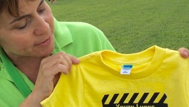 "In this Aug. 2, 2016 photo, Karen Karten, coordinator at the Somerset County Judy Center, shows visitors to the National Night Out event a t-shirt that promotes a tobacco-free environment for young children. The bright, work-zone yellow shirts announce ""Young Lungs Under Construction,"" and are part of the center's Healthy Bodies initiative for children through age 3."