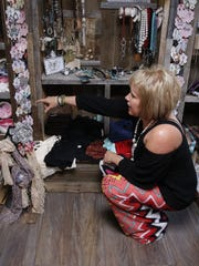 Sheila Mobley, owner of Detailz Mobile Boutique, shows off some of the merchandise in her bus at the Ladies Day Pop Up Event held last Saturday at The Force 2.0 studio in Farmington.