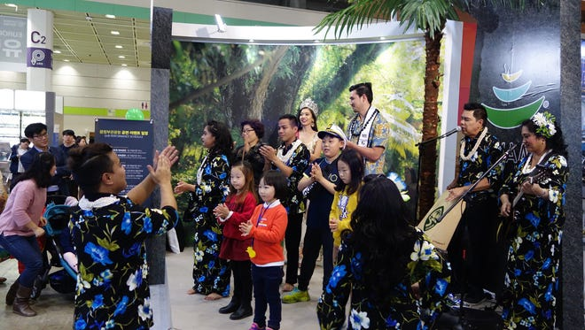 Jesse and Ruby, on the right, and Guam cultural dancers perform with attendees at the Guam booth at the fourth annual Mode Tour Travel Mart held in Seoul, South Korea.