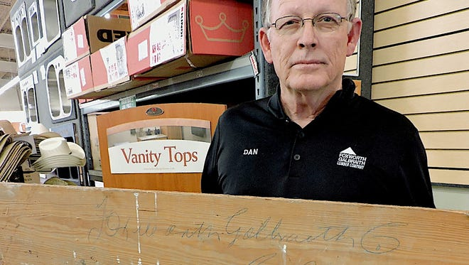 """Dan Lucas, General Manager of Foxworth-Galbraith Lumber Company in Deming, holds a board that was recently removed from a house in Columbus that survived the 1916 Pancho Villa raid. The homeowner donated the board to Lucas at the Deming, Foxworth store. Penciled on the back in flowing script are the words """"Foxworth Galbraith Co, Columbus."""""""