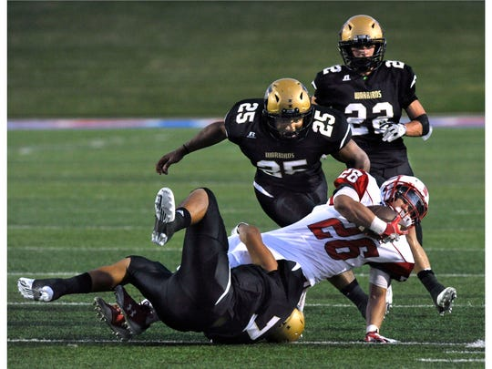 Abilene High School linebacker A.J. Gonzales rolls onto his back as he takes down Odessa High's Josh Lara, while fellow Eagle linebacker Devin Romero and defensive back Doak Holloway rush in to help. The Eagles played the Bronchos Thursday evening Sept. 21, 2017, winning 31-21.