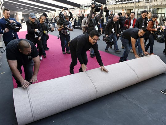 Crew members are trailed by media as they roll out the red carpet for Sunday's 90th Academy Awards in front of the Dolby Theatre on Wednesday, Feb. 28, 2018, in Los Angeles. (Photo by Chris Pizzello/Invision/AP)