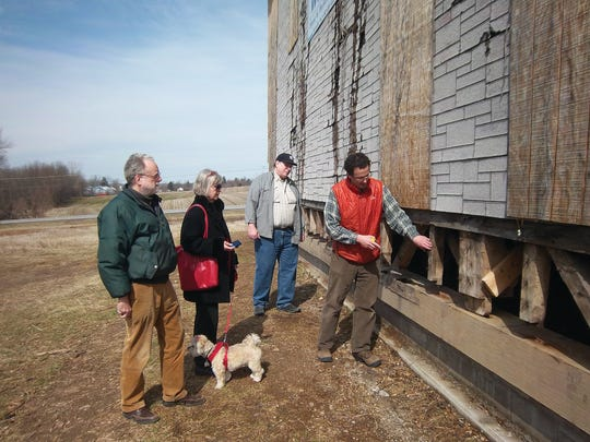 Historic preservation consultant Peter Trieb (right) explains how some of the original 1816 timbers will fit into new construction to Douglas Fisher, Judith Wellman and Charles Lenhart, board members of the nonprofit group that has formed to restore the Quaker Meetinghouse.