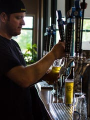 Chris Capetz pours two pints at Goodwater Brewery in
