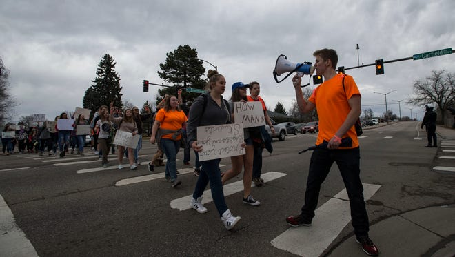 Loveland High School junior Ehret Nottingham leads a march to Dwayne Webster Veteran's Park during a school walkout on Friday, March 23, 2018, in Loveland, Colo.