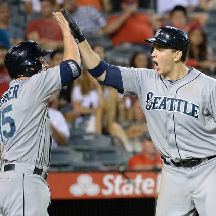 Sep 18, 2014; Anaheim, CA, USA; Seattle Mariners third baseman Kyle Seager (15) (left) celebrates with Seattle Mariners first baseman Logan Morrison (20) (right) after Morrison hit a three-run home run against the Los Angeles Angels during the ninth inning at Angel Stadium of Anaheim. Mandatory Credit: Richard Mackson-USA TODAY Sports
