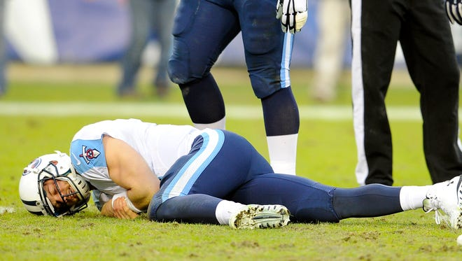 Titans quarterback Jake Locker (10) lies on the field after being injured during the second quarter Sunday.