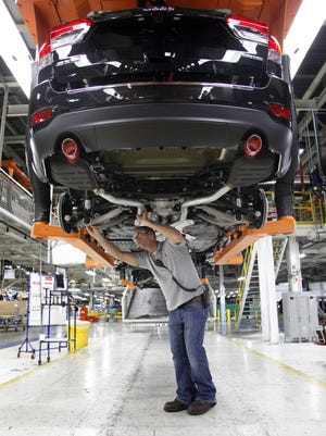 FILE - In this Wednesday, May 8, 2013 file photo, Jeff Caldwell, 29, right, a chassis assembly line supervisor, checks a vehicle on the assembly line at the Chrysler Jefferson North Assembly plant in Detroit. (AP Photo/Paul Sancya)