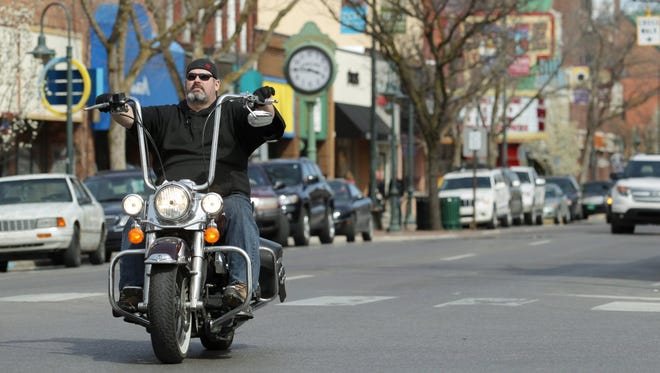 A motorcyclist travels  on East Front Street, Friday, April 13, 2012 in downtown Traverse City, Mich.