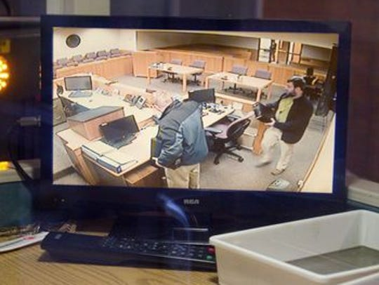 Courtroom security monitors visible from outside the