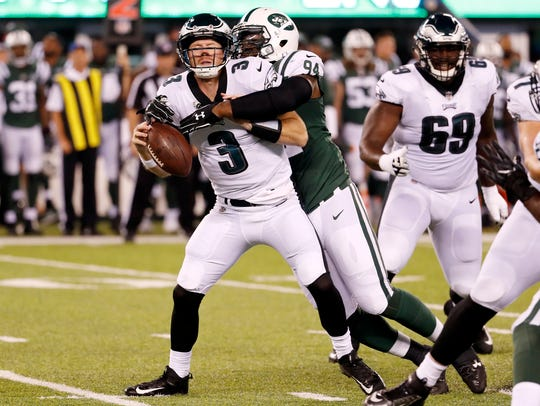 New York Jets defensive lineman Kony Ealy, right, forces