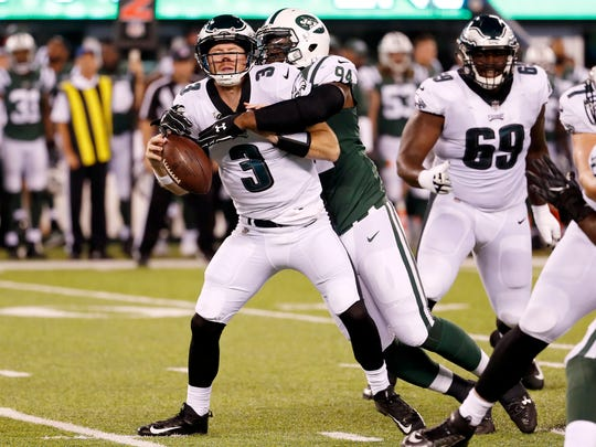 New York Jets defensive lineman Kony Ealy, right, forces a fumble as he sacks Philadelphia Eagles quarterback Matt McGloin during the first half of an NFL football game, Thursday, Aug. 31, 2017, in East Rutherford, N.J. (AP Photo/Michael Noble Jr.)
