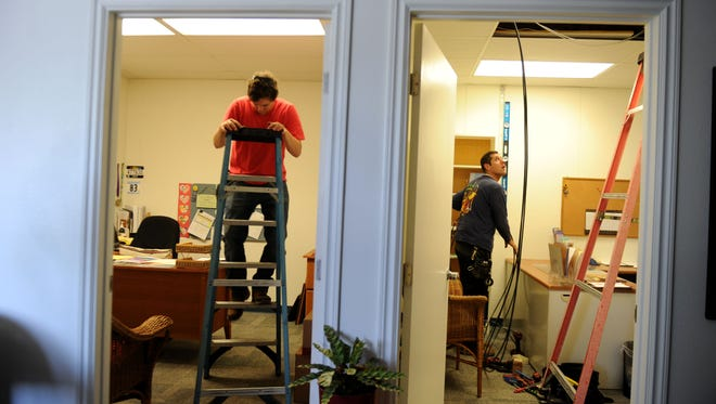 Brian Drippo, left, and Daniel Martinez, with Pacificom, install internet cable in one of the offices at the Pleasant Valley School of Engineering and Arts. The school is moving into the remodeled campus.