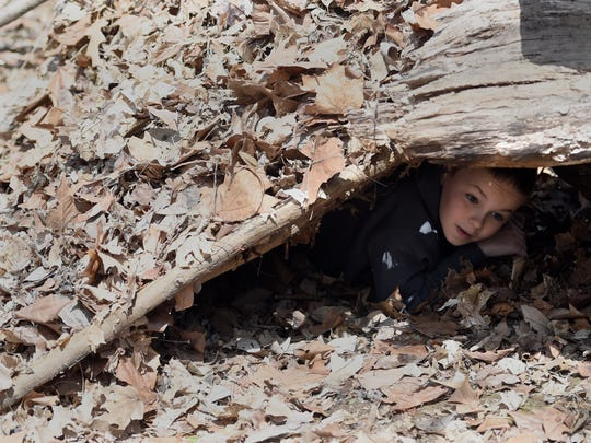 Ben Vondrasek, 10, of Henderson crawls out of a debris