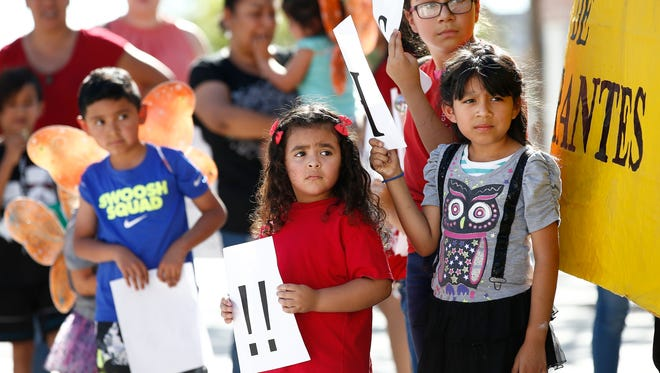 Children listen to speakers during an immigration family separation protest in front of the Sandra Day O'Connor U.S. District Court building, on June 18, 2018, in Phoenix.