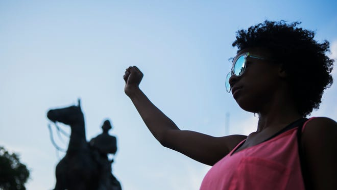 August 12, 2017 - Elechi Egwuekwe, 16, clenches her fist as she stands in front of the Nathan Bedford Forrest statue in Health Sciences Park at the conclusion of a protest showing support for those who were injured or lost their lives on Saturday in Charlottesville, VA. One of the three persons who died was hit by a vehicle that plowed through a group of protestors following a white nationalist rally. The other two victims were officers from the Virginia State Police Department who were involved in a helicopter crash outside of Charlottesville.