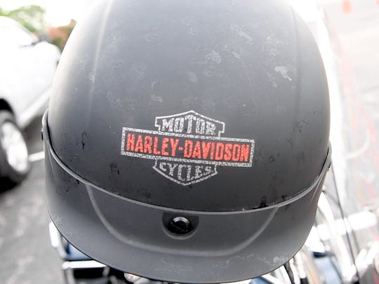 A Harley-Davidson helmet rests on the handle bars of a motorcycle.