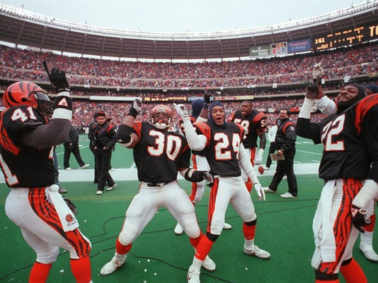 """Text: 1999.1209.06.01 BENGALS 1989 FILE PHOTOGRAPH The Cincinnati Bengals, with #30 Ickey Woods lead the way, join in the """"Ickey Shuffle"""" as the Bengals scored early on the Buffalo Bills in the AFC Championshiop game at Riverfront Stadium. #24 Lewis Billup"""