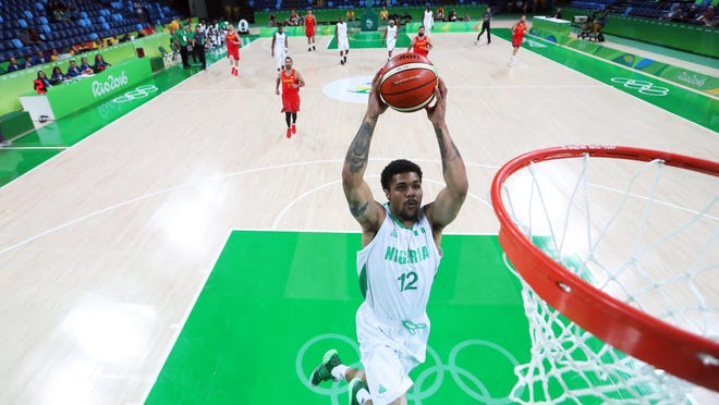 Nigeria's Michael Gbinije (12) drives to the basket at the 2016 Summer Olympics in Rio de Janeiro, Brazil. This is an endline view of what a FIBA basketball court looks like.
