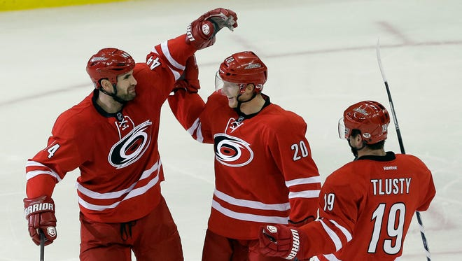 Carolina Hurricanes players Jay Harrison (44), Riley Nash (20) and Jiri Tlusty (19) celebrate Nash's goal against the San Jose Sharks during the third period of an NHL hockey game in Raleigh, N.C., Friday, Dec. 6, 2013.