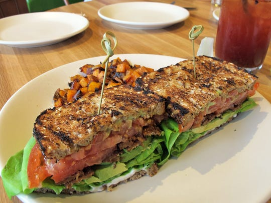 The T.L.T. sandwich replaces bacon in a traditional B.L.T. with smoked tempeh, and is accompanied here by sweet potato hash, at True Food Kitchen in Waterside Shops in Naples.