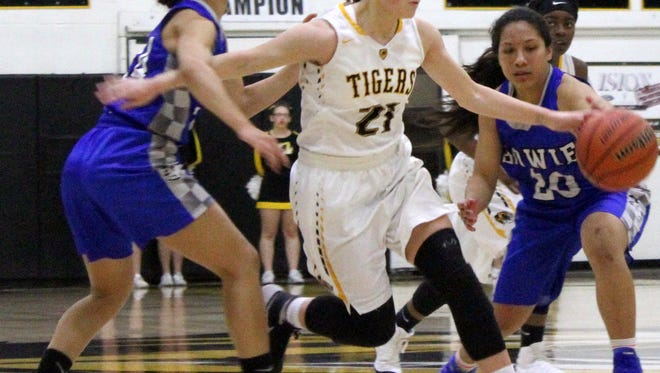 Alamogordo's Calysta Jacob, center, dribbles through a pair of El Paso Bowie defenders Thursday night at the Tiger Pit.