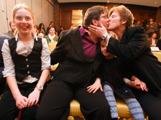 Dawn BarbouRoske, second from left, of Iowa City, kisses her partner, Jen BarbouRoske after learning of the Iowa Supreme Court ruling in favor of legalizing gay marriage in Iowa Friday, April 3, 2009 in Des Moines. Between them is their daughter Bre, 6. Their other daughter, McKinley, 11, reacts to the ruling a left.