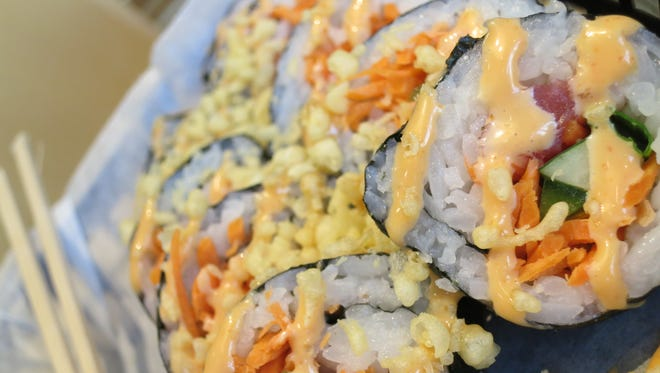 A spicy tuna roll (seaweed wrap, tuna, cucumber, green onion, carrots and jalapeños, with spicy mayo and tempura crunch on top) from Blue Koi.