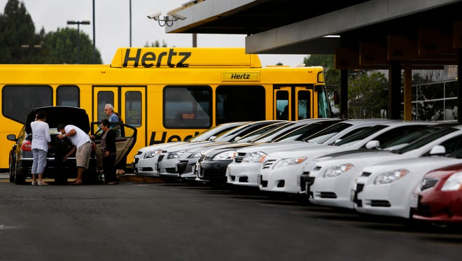 Passengers put luggage in the trunk of a Hertz rental car at Los Angeles International Airport.