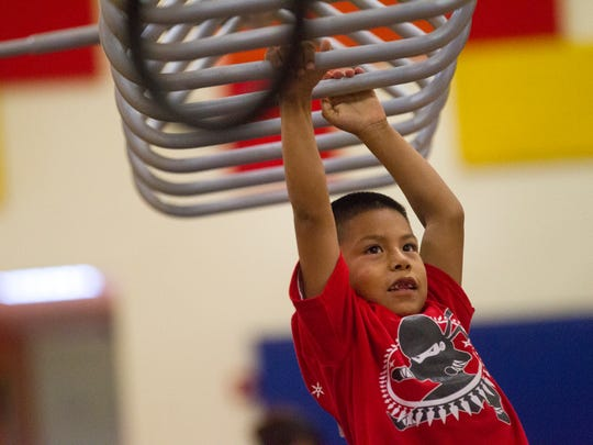 Wesley Atcitty, 6, traverses his way across an obstacle Friday during the Navajo Ninja Kids Competition at the Shiprock Youth Complex.