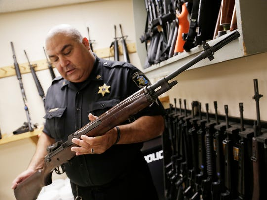 Macomb County Sheriff Sgt. Phil Abdoo shows an M14 rifle July 17 that was acquired through a federal government program.