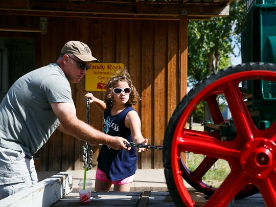 Tim Dezotell and his daughter Olivia, 10, pull the chains off Dezotell's 1930s Hart-Parr Tractor at Powerland Heritage Park on Friday, July 20, 2018. Dezotell's grandfather Percy was one of the founding members of the park, which features 14 museums over more than 60 acres and displays machinery from agricultural history.