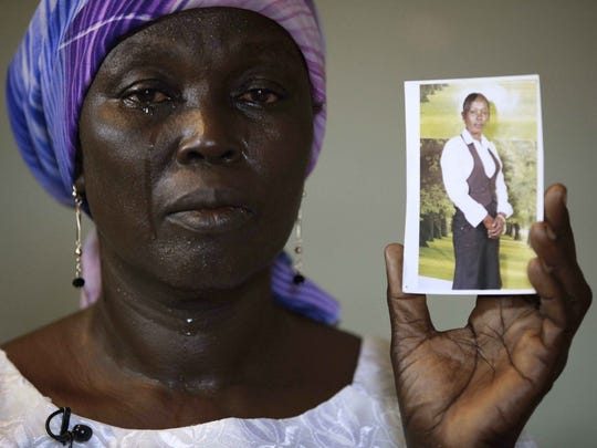 """FILE - In this Monday, May 19, 2014 file photo, Martha Mark, the mother of kidnapped school girl Monica Mark cries as she displays her photo, in the family house, in Chibok, Nigeria. In a new video released late Friday night Oct. 31, 2014, the leader of Nigeria's Islamic extremist group Boko Haram,  Abubakar Shekau dashed hopes for a prisoner exchange to get the girls released. """"The issue of the girls is long forgotten because I have long ago married them off,"""" he said, laughing. (AP Photo/Sunday Alamba, File)"""