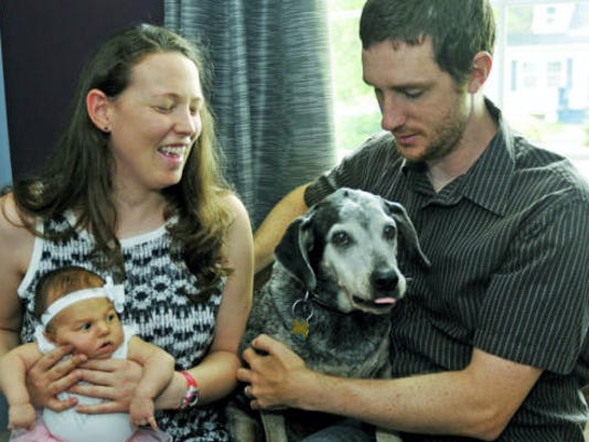 Bouquet, who the family calls Boo for short, is reunited with his owners Kyle Smith, Arys O'Brien and their baby, Inga Smith, 4 weeks old, as seen Monday, July 27, 2015 in Chambersburg.