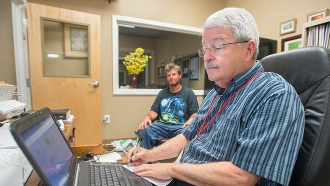 John Findlay, right, processes information Robert PItts' information in order to create an ID for him at the Waterfront Rescue Mission in Pensacola on Wednesday, May 31, 2017.