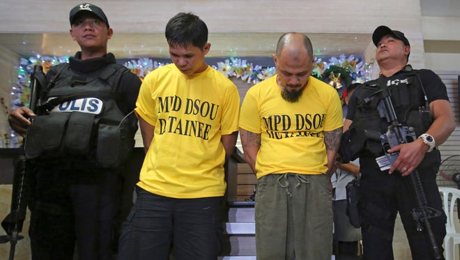 Police secure suspected bombers, Jiaher Guinar, center left, and Rashid Kilala, center right, as they are presented to reporters at police headquarters in Quezon city, north of Manila, Philippines on Thursday, Dec. 1, 2016.