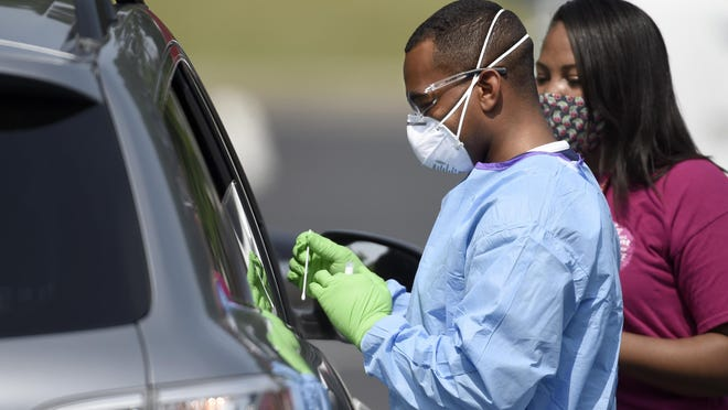 Augusta Fire Department EMS Chief James Kelly gets out the long swab for a COVID-19 test during drive-up testing at Good Shepherd Baptist Church in Augusta, Ga., Friday morning May 22, 2020.
